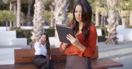 browses: Stylish attractive young businesswoman using a tablet outdoors in an urban square concentrating as she browses the internet  close up upper body