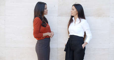 bilateral: Two chic relaxed young women standing chatting together in front of a white exterior wall with bilateral copyspace  three quarter pose