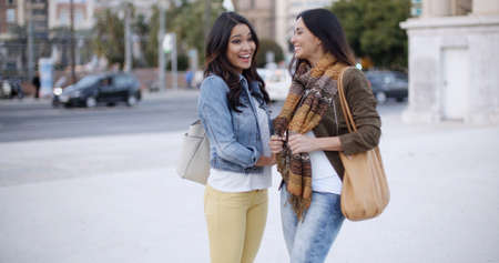 facing each other: Two stylish smiling young women standing facing each other chatting outdoors in a town square  head and shoulders in winter fashion