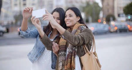 free time: Two gorgeous women posing together for a selfie on a mobile phone as they stand outdoors in an urban square or park