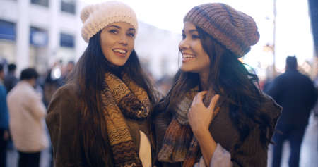 free time: Two stylish young women in winter fashion standing outdoors in an urban street laughing and chatting  upper body pose