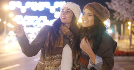 winter fashion: Two vivacious attractive young women in winter fashion standing outdoors in a brightly lit urban street laughing and having fun  close up upper body view