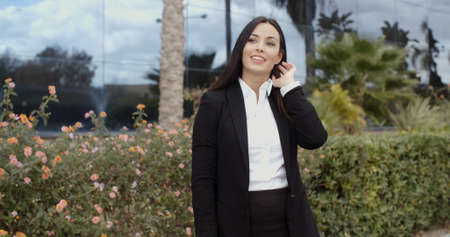 woman business suit: Charismatic stylish young businesswoman standing on the sidewalk outside a modern office building smiling at the camera Stock Photo