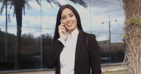 thirties: Confident businesswoman talking on her mobile phone as she stands in front of a modern glass fronted office building  upper body