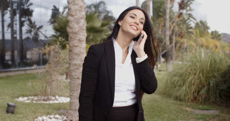 vivacious: Laughing vivacious stylish young businesswoman talking on a mobile phone outside a modern office block  close up head and shoulders Stock Photo