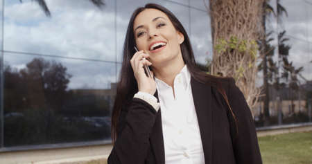 Office women: Laughing vivacious stylish young businesswoman talking on a mobile phone outside a modern office block  close up head and shoulders Stock Photo