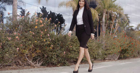 striding: Smiling confident elegant young businesswoman striding along a sidewalk in front of a modern office block smiling at the camera