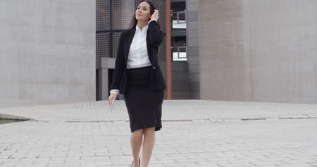 middle age women: Young businesswoman walking towards the camera as she exits her office building while chatting on her mobile phone