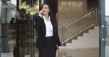 foyer: Young businesswoman taking a mobile phone call as she stands in the foyer of her office building listening to the conversation with a smile