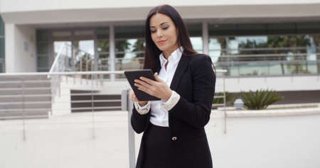 fourties: Stylish businesswoman using her tablet computer as she stands in an urban square or forecourt reading information with a serious expression  with copy space Stock Photo