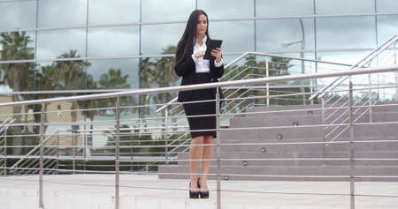 somebody: Young businesswoman holding a tablet-pc standing on a walkway of a modern office building looking to the side as though waiting for somebody  with copy space.