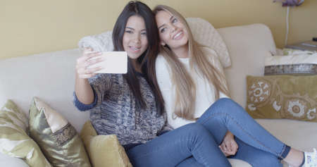 sexy photo: Two young girlfriends taking a selfie on a mobile phone at home as they relax together on a sofa posing and smiling for the camera Stock Photo
