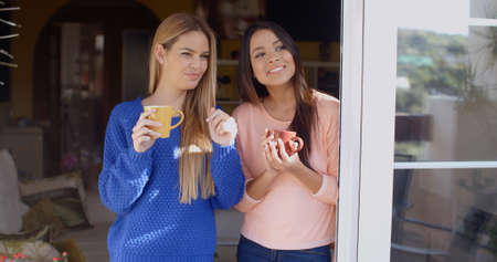 looking through window: Two smiling attractive young women standing drinking coffee and looking through a window or open glass patio door
