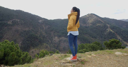red shoes: Cute young woman in yellow coat and red shoes looking out into mountain valley on cold day