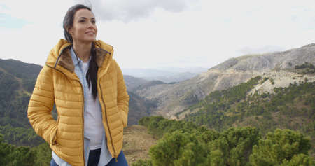 appreciating: Smiling woman appreciating the peace of nature as she stands high above a mountain valley smiling happily to herself  with copy space