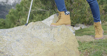sturdy: Active person wearing sturdy hiking boots hiking in rock terrain with poles stepping onto a rock  close up of the feet in jeans