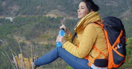 isotonic: Young attractive female backpacker pausing for a drink of bottled water on a mountain trail overlooking a valley  close up side view