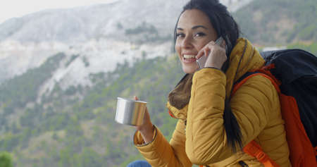 Enthusiastic young female hiker in yellow coat with backpack and walking sticks drinking and talking on phone in mountains Stock Photo