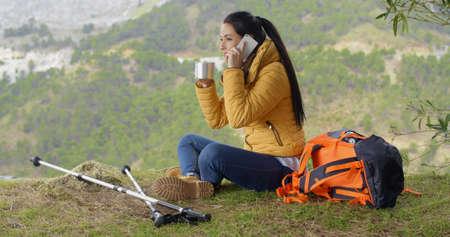 hablando por telefono: excursionista mujer joven muy contento con la naranja mochila y bastones en el teléfono agitando la mano