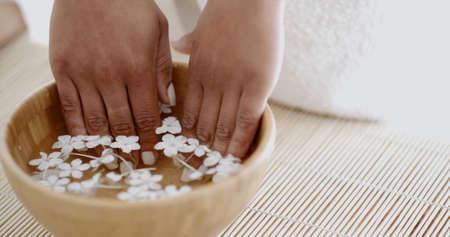Hände mit Maniküre in der Schüssel Wasser mit Blumen Blütenblätter entspannen