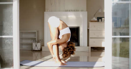 sexual position: Slender athletic girl doing yoga exercises indoor