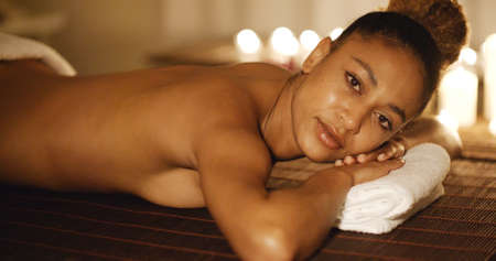 sensual massage: Lovely young african-american woman relaxing with candles on the background