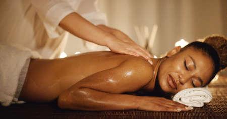 mujer que tiene la terapia de masaje afroamericano de nuevo en la cámara lenta salón del balneario