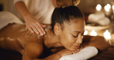 sensual massage: African-american woman getting a relaxing massage in salon in slow motion
