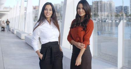 mujeres elegantes: Dos mujeres adorables que se colocan en el Paseo Marítimo de Málaga Muelle y mirando a la cámara que llevaba ropa formal de negocios elegantes sonriendo Foto de archivo