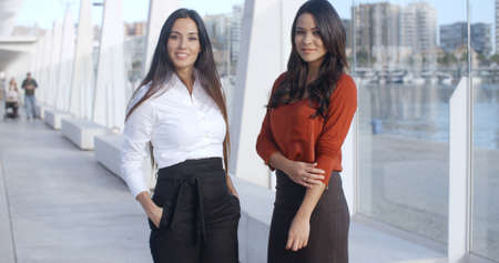 women business: Two Adorable Women Standing at Promenade in Malaga Pier and looking at camera  they wearing formal business elegant clothes  smiling