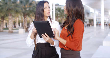 consternation: Two attractive young woman standing looking at a tablet outdoors in an urban street with looks of consternation  upper body close up Stock Photo
