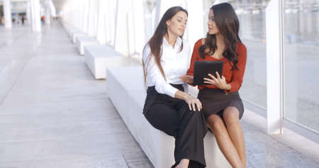 Two city business women enjoying an informal meeting sitting outdoors in a long promenade discussing information on a tablet computer