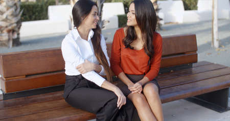 sitting pretty: Two stylish female friends sitting on a wooden bench chatting and laughing together in an urban square