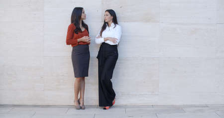 bilateral: Two fashionable young women standing leaning on a white wall chatting outdoors  bilateral copyspace