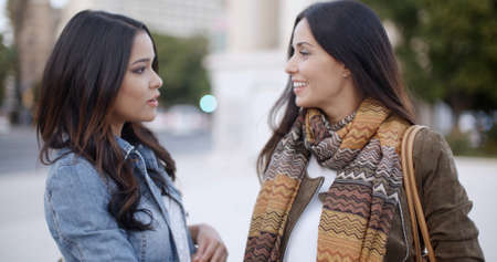 winter fashion: Two stylish smiling young women standing facing each other chatting outdoors in a town square  head and shoulders in winter fashion