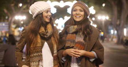 Two young woman enjoying a winter night out together as they stand chatting in a brightly lit urban street in trendy winter outfits