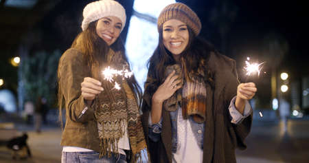 women smiling: Attractive young women having fun at Christmas standing outdoors in stylish winter outfits at night smiling and laughing with sparklers in their hands