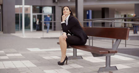 confident business woman: Confident young business woman sitting alone on bench outside office building with calm expression Stock Photo