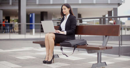 casual wear: Business woman sitting alone on bench with bag and using laptop computer near office building Stock Photo