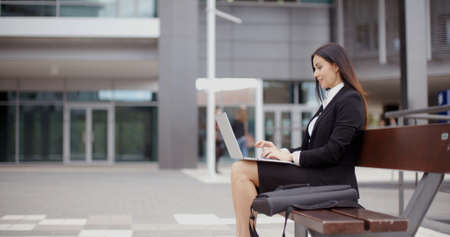near side: Side view of business woman sitting alone on bench with bag and using laptop computer near building