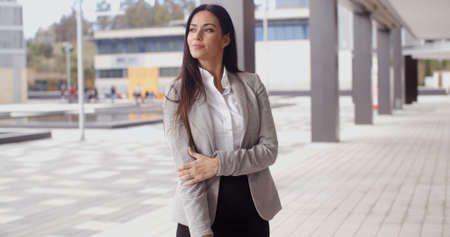 casual wear: Beautiful optimistic Caucasian business woman standing outdoors holding her arm and looking out with grin