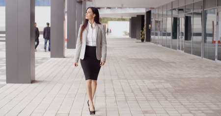 Beautiful confident Caucasian business woman with grin walking outdoors near office building
