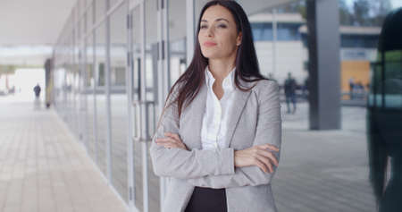 confident business woman: Confident business woman with grin standing outside of office building with folded arms