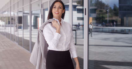 Independent beautiful business woman standing outside of office building with folded arms and jacket over shoulder Stock Photo