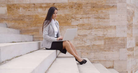 stone steps: Low angle view of cute business woman sitting alone on marble staircase outdoors with laptop