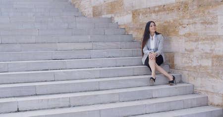 mujeres elegantes: Mujer de negocios joven linda con tacones altos sentado al aire libre en la escalera con las piernas cruzadas Foto de archivo