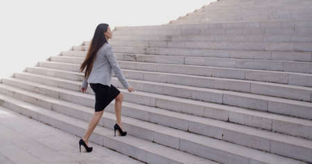 Serious young business woman in high heel shoes walking up long flight of marble stairs outdoors Stockfoto