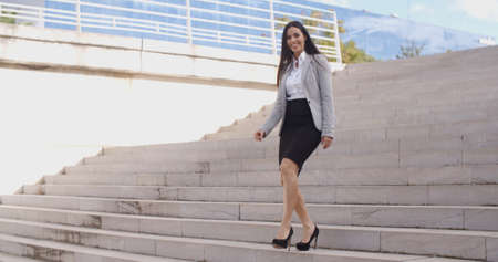 stairs: Smiling young business woman in high heels walking down flight of marble stairs outdoors Stock Photo
