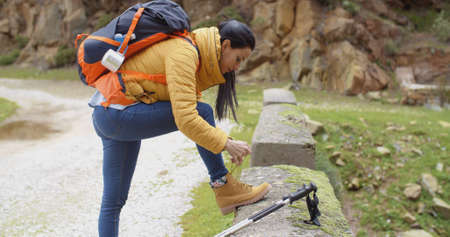 sturdy: Female hiker tying her laces on a sturdy pair of hiking boots as she pauses on a mountain trail  facing camera with copy space Stock Photo