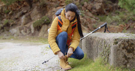 facing on camera: Female hiker tying her laces on a sturdy pair of hiking boots as she pauses on a mountain trail  facing camera with copy space Stock Photo